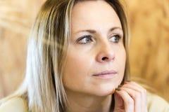 Authentisches nachdenkliches blondes junges Porträt der erwachsenen Frau Stockfotos