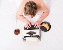 Author guy tousled hair busy write chapter deadline coming top view. Man inspired lay bedclothes work book. Writer. Author used old fashioned typewriter. Man stock photo