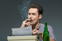 Author smoking cigar and drinking alcohol at Royalty Free Stock Photos