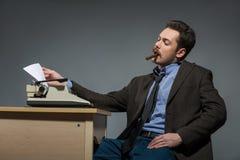 Author smoking cigar at typewriter Royalty Free Stock Image