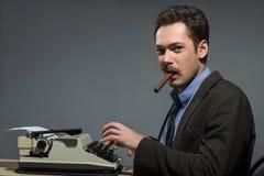 Author smoking cigar at typewriter Royalty Free Stock Photos