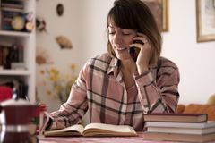Author talking with publisher. Young female book author sitting on her desk and talking on phone with publisher Stock Photos