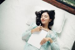 Author, Typewriter, Journalist. Intelligent woman lying on bed a royalty free stock photo