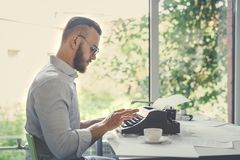 Author at work. Young hipster at work indoors stock photography