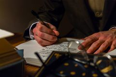 Author writing in a journal taking notes about stories or ideas. Shot of hands writing in a book on a table surrounded by novels royalty free stock photo