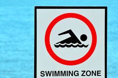 Authorise swimming zone sign. Against blue water background royalty free stock image