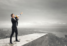 Authoritarian announcement to the megaphone. Businessman authoritarian announcement to the megaphone from above a roof Royalty Free Stock Images