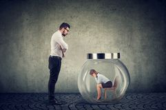 Authoritarian boss businessman looking at a glass jar with captured woman inside royalty free stock photography
