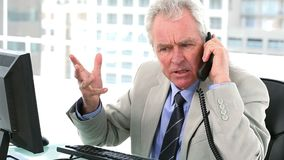 Authoritarian boss on the phone. Sitting in his office stock footage