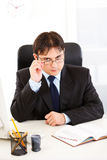 Authoritative businessman straightening eyeglasses Royalty Free Stock Photography
