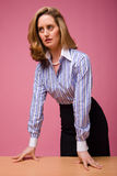 Authoritative woman in striped shirt. Leaning on desk on pink background Stock Photo