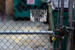 Authorized personnel sign on a chain link fence with dumpsters. In the background stock image
