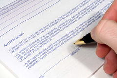 Authorized Signature. This is an image of a hand with a pen signing an authroization form royalty free stock images
