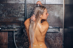 Autiful woman standing at the shower. is washing her hair. Royalty Free Stock Photography