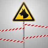 Aution - danger Be aware of dogs The area is guarded by dogs. Warning sign safety. The sign on the pole and warning bands. Gray ba Royalty Free Stock Photos