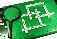 Autism. Concept with game board and magnifying glass Stock Photos