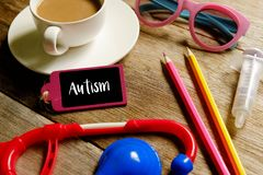 Autism awareness. For blog title and header. Kids stethoscope,sunglasses,syringe,pencils and wooden board with word AUTISM on wooden table stock image