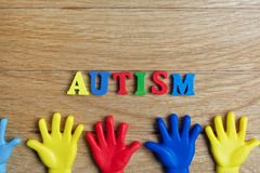 Autism awareness concept with colorful hands on wooden background. Top view. Autism awareness concept with colorful hands on wooden background Stock Photo