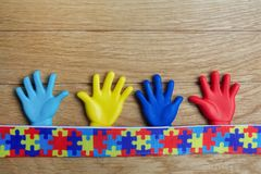Autism awareness concept with colorful hands on wooden background. Top view. Autism awareness concept with colorful hands on wooden background Stock Images
