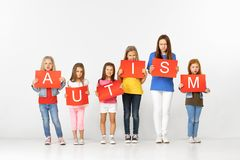Autism. Group of children with red banners isolated in white. Autism - dont be scared to be different. Group of angry sad children with red banners isolated in royalty free stock photography