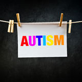 Autism printed on paper. Hanging on rope. Concept image for disorder of neural development Stock Photography