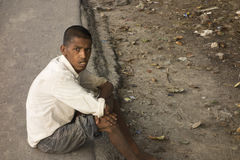 Autism profile hopeless poor boy sitting in road Stock Photo