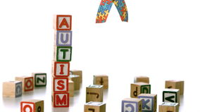Autism ribbon falling beside blocks spelling autism Stock Image