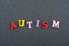 AUTISM word on black board background composed from colorful abc alphabet block wooden letters, copy space for ad text Stock Photo