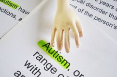 Word AUTISM , close up. Autism word on  paper texture with artificial human hand Royalty Free Stock Image
