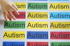 Word AUTISM , close up. Autism word on paper texture with artificial human hand Stock Photo