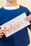 Autism. Young boy (children hands) hold Autism text written on sheet of paper close up Royalty Free Stock Photos