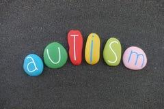 Autismo, desorden del espectro del autismo, nombre de la enfermedad compuesto con las piedras coloreadas sobre la arena negra libre illustration