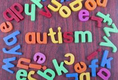 Autismtext med spridda alfabet woden på tabellen Arkivfoton