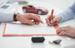 Autista che firma un'assicurazione auto fotografie stock libere da diritti