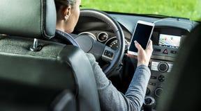 Autista che utilizza smartphone e navigazione dei gps in un'automobile Fotografia Stock