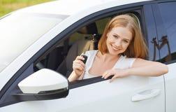 Autista della donna con le chiavi che conducono una nuova automobile Fotografie Stock