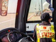 Autista di autobus che si siede vicino al volante sul bus di navetta in aeroporto immagini stock libere da diritti