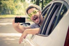 Autista di automobile che mostra smartphone con lo schermo in bianco immagini stock libere da diritti
