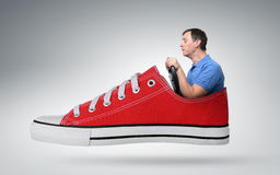 Autista di automobile divertente dell'uomo con una ruota in scarpa da tennis rossa Immagine Stock Libera da Diritti
