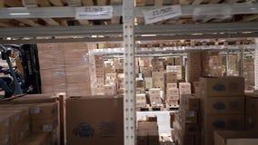 Autista di camion del carrello elevatore in una fabbrica o in un magazzino che guida fra le file della scaffalatura con le pile d Fotografie Stock