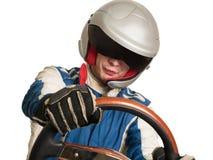 Autista di macchina da corsa nel casco mentre guidando Su una priorità bassa bianca fotografia stock
