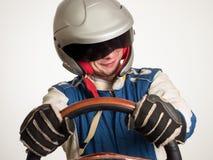 Autista di macchina da corsa nel casco mentre guidando Su una priorità bassa bianca immagini stock
