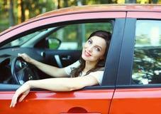 Autista grazioso della giovane donna dietro l'automobile di rosso della ruota Immagine Stock