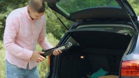 Autista maschio che prende la presa dell'automobile dal tronco aperto stock footage