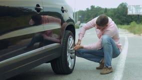 Autista maschio che svita la ruota di automobile dalla chiave sulla strada video d archivio
