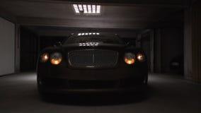 Autista professionista che collauda nuova automobile costosa in garage, inserentesi i fari archivi video