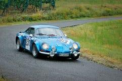 Autisti non identificati su una vettura da corsa alpina d'annata blu di Renault Fotografie Stock