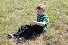 Autistic Boy Sitting in a Field Stock Photography