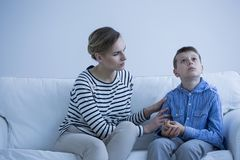 Autistic boy and carer. Autistic boy sitting on a sofa with his carer trying to calm him down royalty free stock images