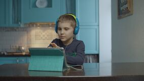 Autistic boy using tablet computer with headphones on the kitchen. Kid with autism looking around at home. Autism